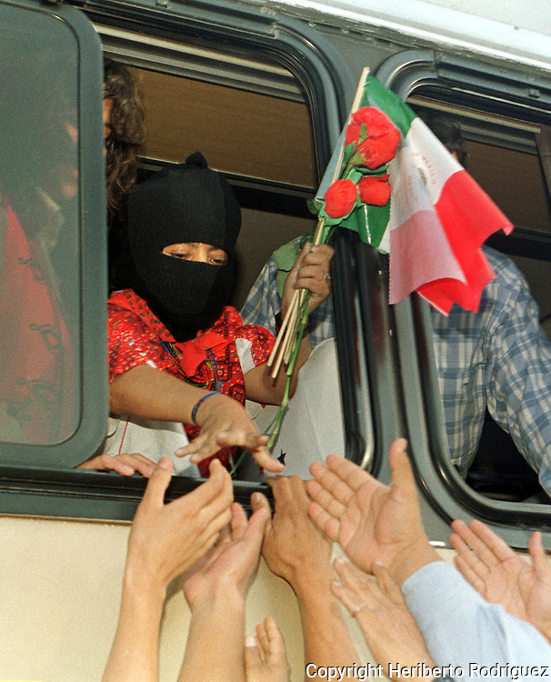 Zapatista commander Ramona holds flowers and a Mexican flag while shaking hands with supporters on her way to the meeting with Indian organizations in Mexico City, October 11, 1996. Ramona attended the closing of the National Indian Congress in Mexico city, where differents Indian organizations took part in advance to struggle for their rights and and the deffense of their cultures. Photo by Heriberto Rodriguez