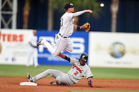Lakeland Flying Tigers second baseman Brandon Loy (10) throws to first jumping over shortstop Orlando Arcia (2) slides in during a game against the Brevard County Manatees on April 10, 2014 at Joker Marchant Stadium in Lakeland, Florida.  Lakeland defeated Brevard County 6-5.  (Mike Janes/Four Seam Images)