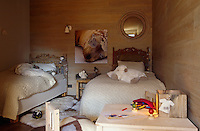 The traditional carved alpine furniture in the children's bedroom contrasts with the modern wood-clad walls