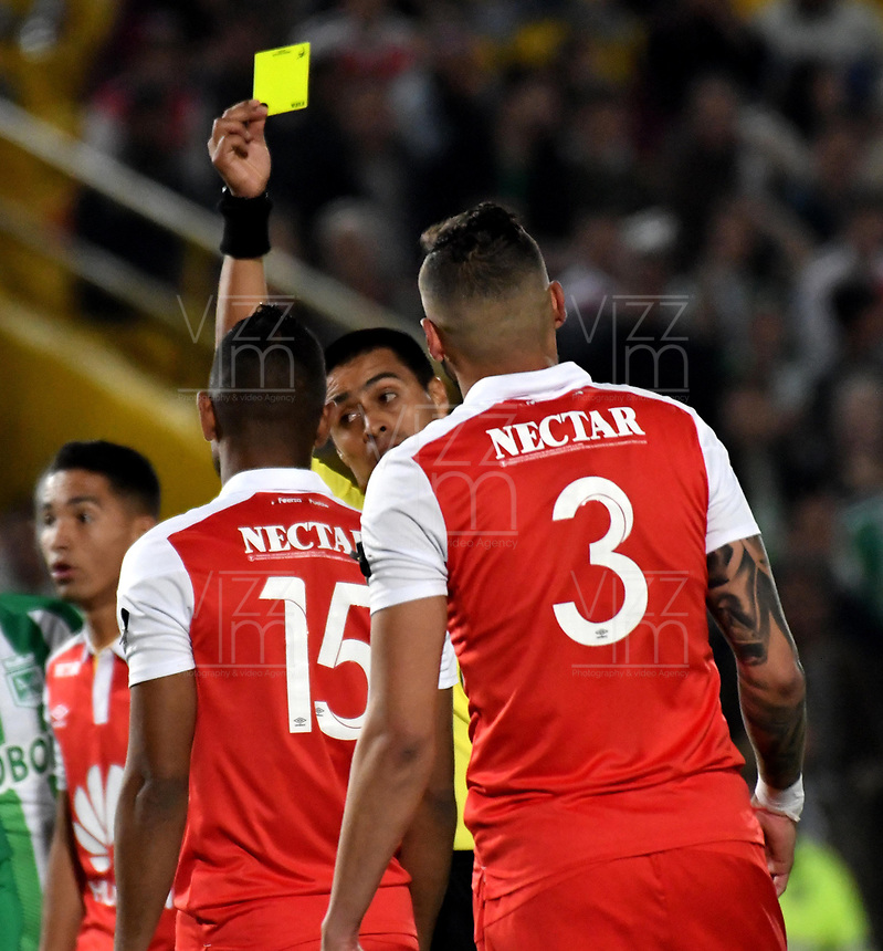 BOGOTÁ - COLOMBIA, 17-01-2019: Ferney Trujillo (Cent.), árbitro, muestra tarjeta amarilla a Martín Payares (Cent.), jugador de Atlético Nacional, durante partido entre Independiente Santa Fe y Atlético Nacional, por el Torneo Fox Sports 2019, jugado en el estadio Nemesio Camacho El Campin de la ciudad de Bogotá. / Ferney Trujillo (C), referee, shows yellow card to Martín Payares (L) player of Atletico Nacional, during a match between Independiente Santa Fe and Atletico Nacional, for the Fox Sports Tournament 2019, played at the Nemesio Camacho El Campin stadium in the city of Bogota. Photo: VizzorImage / Luis Ramírez / Staff.