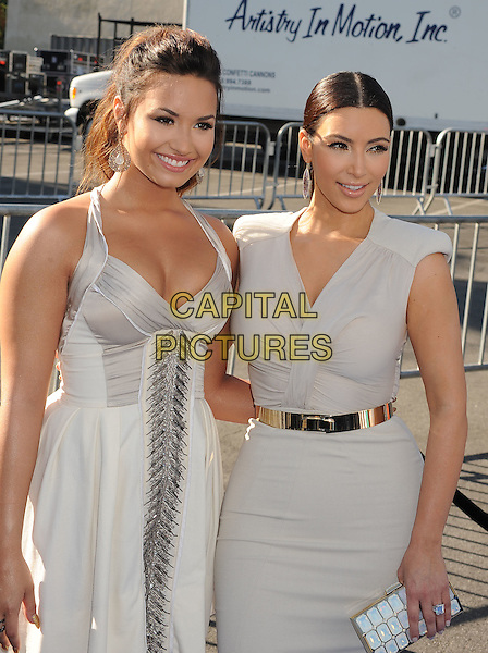 Demi Lovato & Kim Kardashian.The 2011 Do Something Awards held at The Palladium in Hollywood, California, USA..August 14th, 2011.half length white grey gray dress silk satin belt gold beige .CAP/ROT/TM.©Tony Michaels/Roth Stock/Capital Pictures