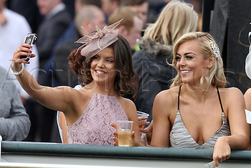 08.04.2016. Aintree, Liverpool, England. Crabbies Grand National Festival Day 2. Racegoers pose for a photo at the rail.