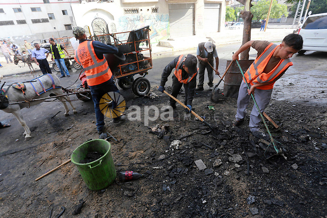 Palestinian workers clean the scene of explosions destroyed five cars in Gaza City July 19, 2015. The spokesman for Gaza's interior ministry said that a number of cars belonging to Palestinian factions were blown up by vandals and the security services started to investigate the incident. Photo by Mohammed Asad