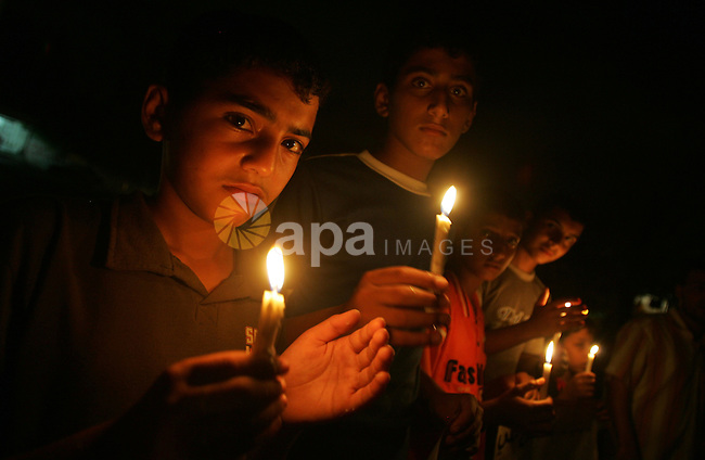 Palestinian children light candles during a protest against a power cut in Gaza City on August 8, 2010. The Gaza Strip's sole power plant shut down on Saturday for lack of diesel fuel, a Palestinian power authority official said. Photo by Ali Jadallah