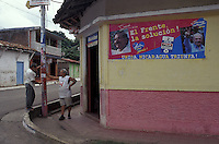 Two men chatting beside an FSLN 2006 presidential elections campaign poster in Moyogalpa on Isla de Ometepe, Nicaragua.