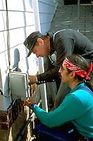 Men age 40 working together on telephone box.  St Paul  Minnesota USA