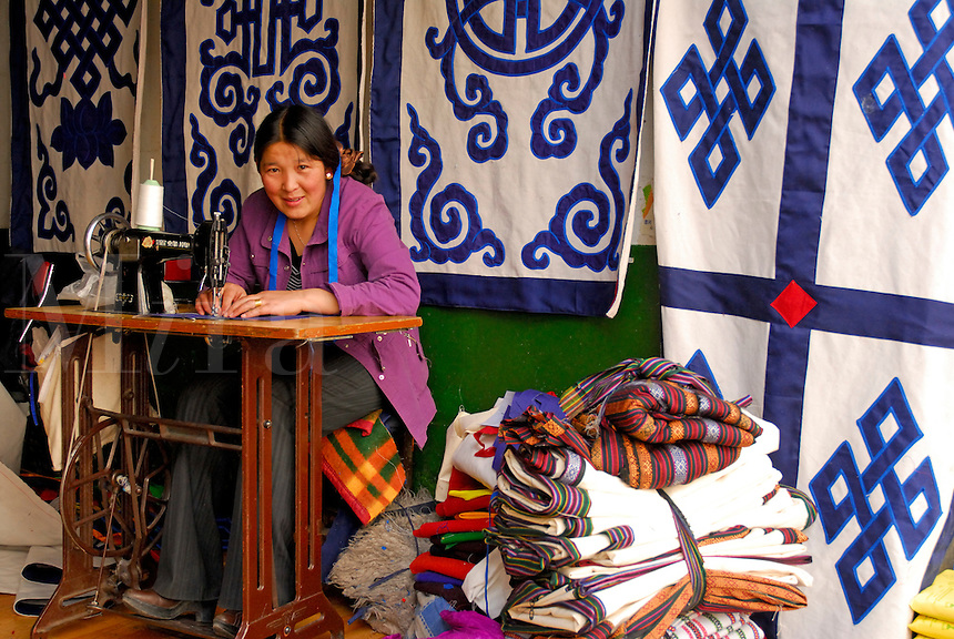 Sewing Tibetan wall hangings, traditional decorations in most Tibetan homes, in the Barkhor, Lhasa, Tibet.  The eternal knot, one of the Eight Auspicious Symbols in Buddhist culture, represents infinite wisdom, compassion, and the interrelatedness of all things.