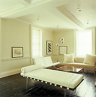 White leather Barcelona seating by Mies van der Rohe surrounds a bespoke coffee table with built-in lights
