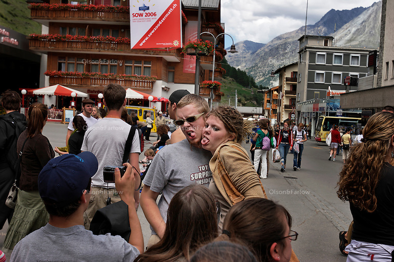 Tourists in the main plaza and on the street in downtown Zermatt.  People must take the train or taxi from outside the city because no cars are allowed in the downtown.