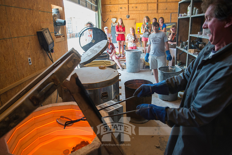 Robert Long removes a camper's ceramic bowl out of a kiln as his assistant Mitch Philips and other campers observe the process through the INvision Visual Arts Summer Program.<br />  (photo by Sarah Dutton / &copy; Mississippi State University)