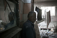 "In this Friday, Aug. 15, 2014 photo, a Palestinian man stands at the living room of his house -where he and his family still living- that was partially destroyed by an israeli airstrike during the ""Protective Edge"" military operation in Shuyaja neighborhood in Gaza City. After a five days truce was declared on 13th August between Hamas and Israel, civilian population went back to what remains from their houses and goods in Gaza Strip. (Photo/Narciso Contreras)"