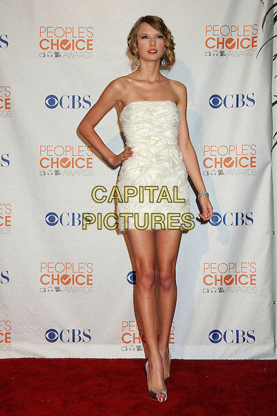 TAYLOR SWIFT .36th Annual People's Choice Awards - Press Room held at the Nokia Theatre LA Live, Los Angeles, California, USA, 6th January 2010..full length strapless white dress hand on hip silver metallic shiny peep toe shoes .CAP/ADM/BP.©Byron Purvis/Admedia/Capital Pictures