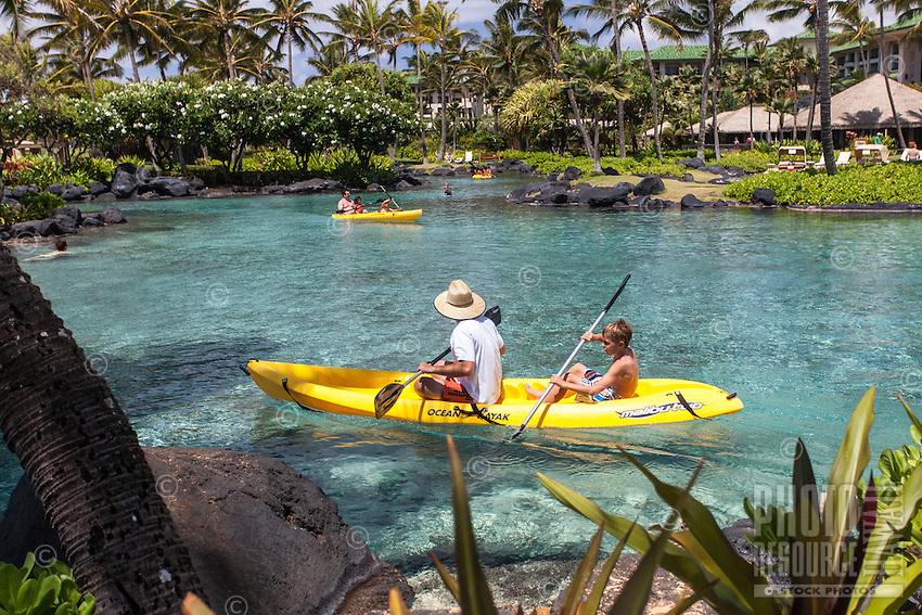 Families kayaking in lagoon at at Grand Hyatt Kauai Resort in Koloa, Kaua'i