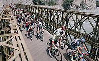 peloton riding over a narrow old bridge in the neutralised section of the race<br /> <br /> 104th Tour de France 2017<br /> Stage 19 - Embrun &rsaquo; Salon-de-Provence (220km)