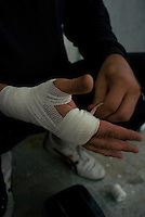 Luis Madhuar prepares his hands before putting o his gloves. Tepito Gym in the Tepito neighbourhood of Mexico City September 18, 2007