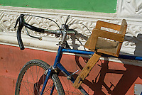 Bicycle with a wooden baby seat parked against a wall, Trinidad, Sancti Spiritus, Cuba.