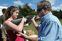 NWA Democrat-Gazette/FLIP PUTTHOFF <br /> Charity Orsi gets coaching Oct. 7 2015 from Lonnie Robinson before donning safety glasses to shoot at clay targets.