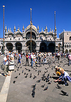 Feeding pigeons in front of the Famous St Marks Church in San Marcos Plaza in romantic Venice Ital