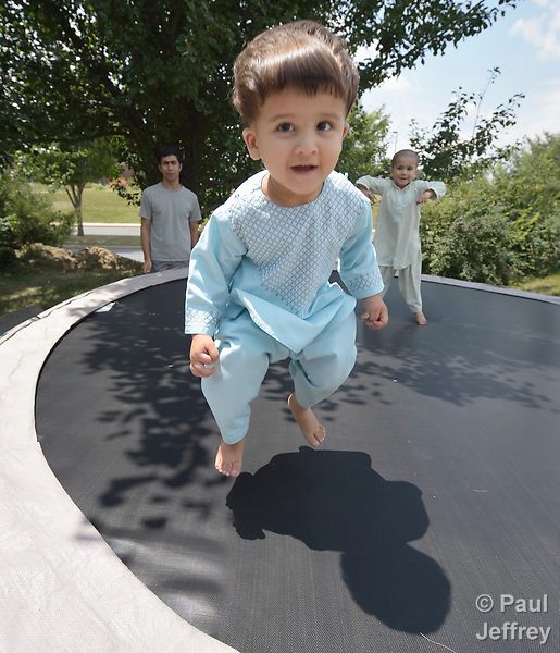 Sanaullah Ahmadzai, 2, bounces on a trampoline with his brother, Nasratullah Ahmadzai, 4, as their father, Ahmadullah Ahmadzai, watches in the yard of their home in Harrisonburg, Virginia. Refugees from Afghanistan, they were resettled in Harrisonburg by Church World Service.<br /> <br /> Photo by Paul Jeffrey for Church World Service.