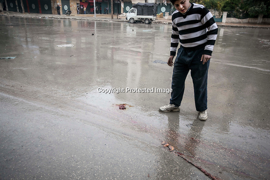 In this Monday, Dec. 17, 2012 photo, a Syrian youth reacts as he watchs the rests of a dead body spread out on the street after a mortar shell landed on a commercial street killing two people in the Bustan Al-Qasr district of Aleppo, Syria. (AP Photo/Narciso Contreras)