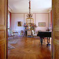 View through open double doors in to the Music Room, home to a grand piano and a collection of Louis XVI chairs bought mainly at auction
