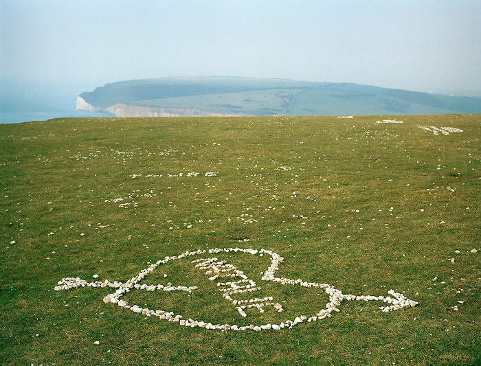 A heart made of chalk fragments in the grass on top of white cliffs at Birling Gap, East Sussex. England.<br />