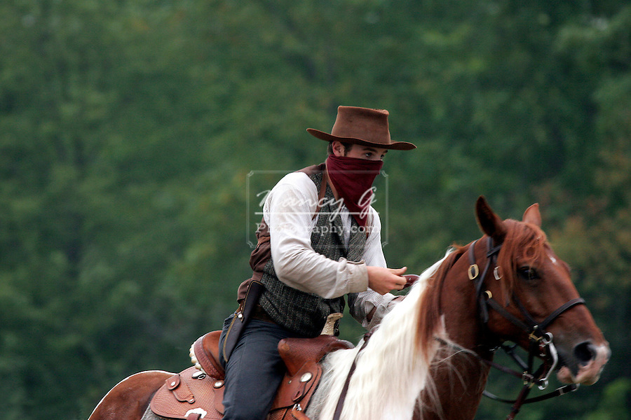 A young male cowboy bandit riding horseback
