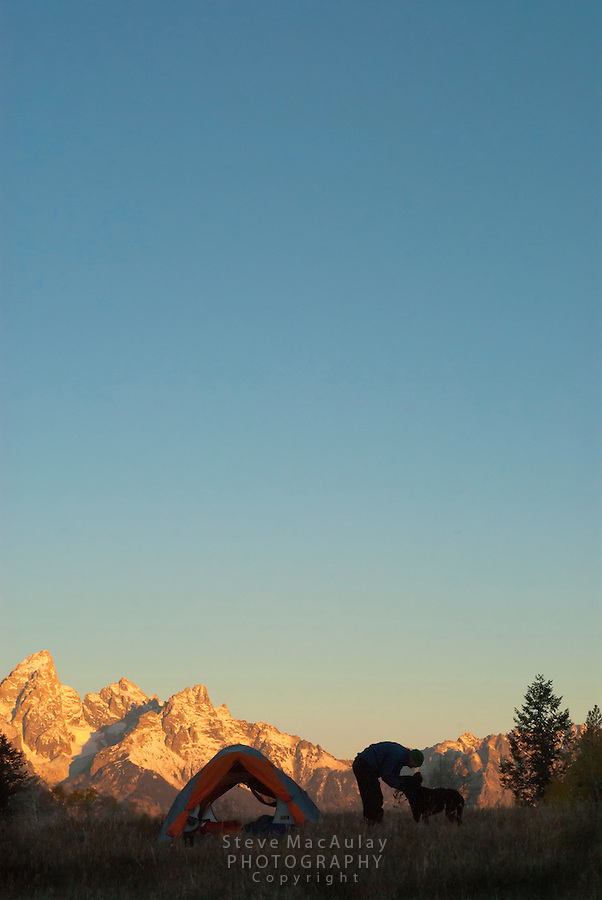 Sunrise on the Grand Tetons, as a man pets his dog next to tent, Grand Teton National Park, Jackson, Wyoming