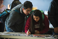 "NWA Democrat-Gazette/J.T. WAMPLER Enrique Carlos (left) and Johana Burciago sign a banner Monday Feb. 13, 2017 at Rogers Heritage High School. The banner reads: ""Heritage United: We are one, divided by none."" Students were encouraged to sign their name and add a message on what unites them as opposed to what divides them."