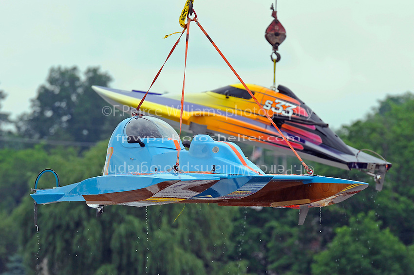 """A modern conventional hydro (foreground) Tony Kreitzer's, S-67 """"Impossible Dream and a now """"coventional"""" cabover boat Doug Martin's,S-33 """"Sunday Money"""" being lifted back to their trailers.  (2.5 Litre Stock hydroplane(s)"""