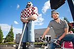 """Michael Jones, a """"transportationalist"""" who owns six bicycles and 5 unicycles, rides his """"tall bike"""" with girlfriend Evelyn Barnes riding on the back, past the Paul Bunyan statue in Portland's Kenton neighborhood.  A tall bike consists of one bicycle frame welded on top of another with vertical and horizontal chain drives and a seat six feet above the ground."""