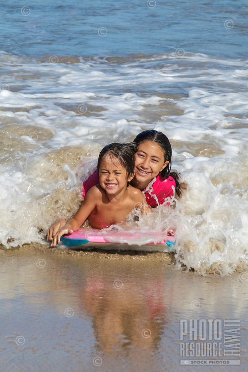 A local brother and sister share a boogie board at Hanalei Bay off of Hanalei Beach, Kaua'i.