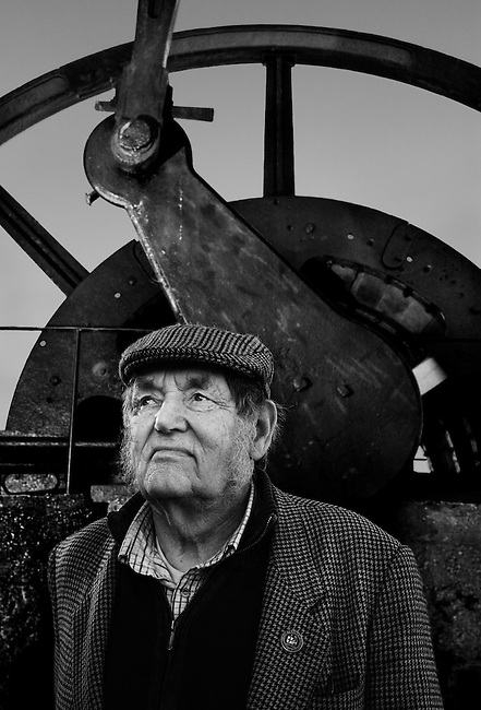 Ken Brown, mining historian, in front of the flywheel of 'Michell's Whim', part of a beam winding engine, Pool, Cornwall.