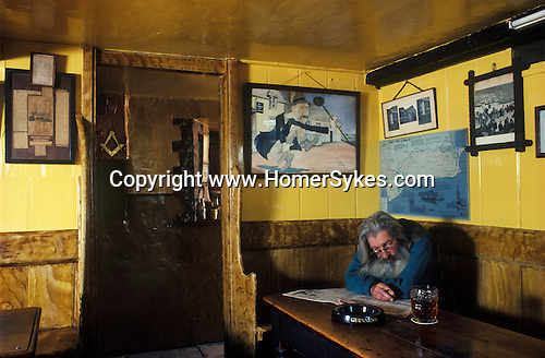 The Village Pub. The Square and Compass, Worth Matravers, Dorset, England. Ray Newman the publican under a portrait of his late father also the publican of this 265 year old public house.
