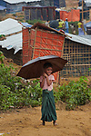 A Rohingya refugee girl holds an umbrella as she walks though the sprawling Kutupalong Refugee Camp near Cox's Bazar, Bangladesh. More than 600,000 Rohingya have fled government-sanctioned violence in Myanmar for safety in Bangladesh.