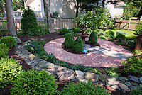 Small circular patio shade garden with patterned brick, blue flagstone, evergreens, hostas, shrubs, trees, picket fence, lawn grass, fountain focal point, stone wall