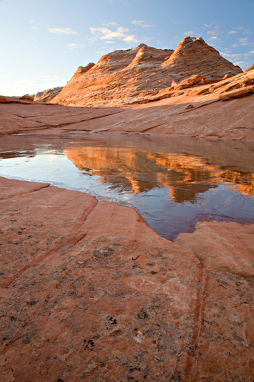 """A water pocket covered in ice reflects sandstone """"teepees"""" common in the Coyote Buttes area."""