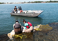 Erin Nicholls said she had to get approval to release names and what they are doing. <br /> <br /> Ministry of the Environment and Climate Change Erin Nicholls, a field co-ordinator of the Great Lakes Unit, Etobicoke, crew chief Ryan Mototsune and University of Guelph environmental engineering student Robert Howard doing a spot tail shiner survey. The three were collecting samples at the mouth of the Talfourd Creek at Shell Corunna.