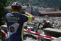 Switzerland. Canton Graubunden. Bregaglia valley. Bondo. A second massive landslide hit Bondo while the remote village was still recovering from a huge landslide caused by a giant rockslide swept down from Piz Cengalo on August 23, 2017. The mudslide smashed the carpentry factory and equipment that was being used to clear debris from the previous landslide. A cyclist wearing a Festina Watches sport shirt takes pictures with his smartphone. 26.08.2017 © 2017 Didier Ruef