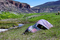 A classic coupe is partially submerged in the creek bed of Echo Creek in Echo Canyon along the Lincoln Highway in eastern Utah.