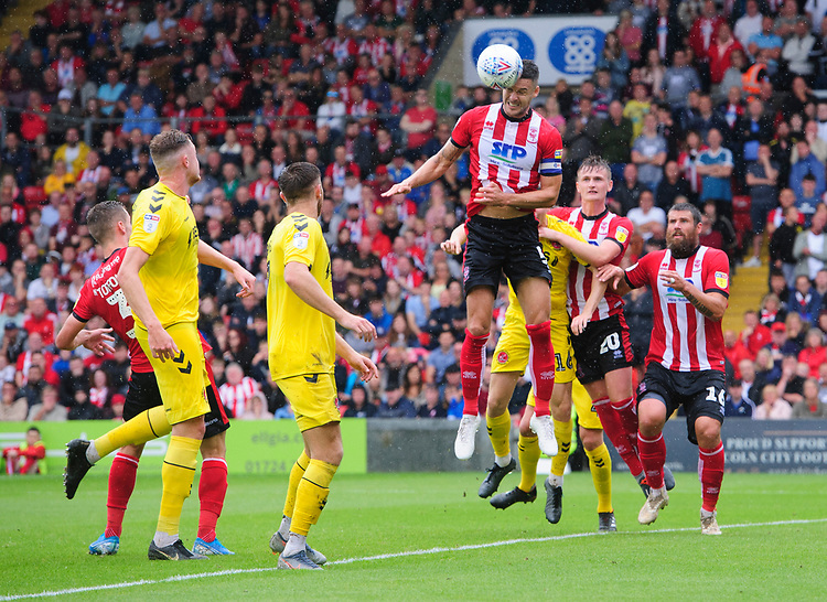 Lincoln City's Jason Shackell heads the ball clear of danger<br /> <br /> Photographer Chris Vaughan/CameraSport<br /> <br /> The EFL Sky Bet League One - Lincoln City v Fleetwood Town - Saturday 31st August 2019 - Sincil Bank - Lincoln<br /> <br /> World Copyright © 2019 CameraSport. All rights reserved. 43 Linden Ave. Countesthorpe. Leicester. England. LE8 5PG - Tel: +44 (0) 116 277 4147 - admin@camerasport.com - www.camerasport.com
