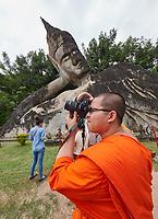 Laos. Buddha Park. A Buddhist monk taking a souvenir photo.