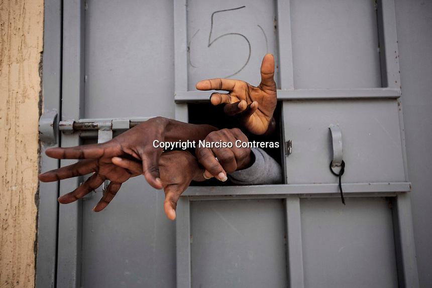 Sub-Saharan illegal migrants and refugees reach through the window of a cell in the Garabuli Detention Centre, pleading for water, cigarettes and food.
