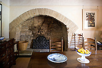 A massive restored stone fireplace dominates the dining room