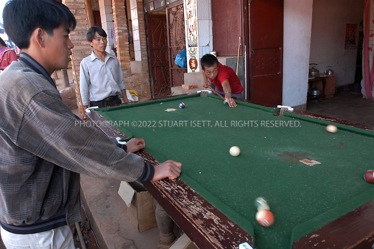 12/3/2004--Ban Lao Village, Yongde County, Yunnan, China..Young men shoot pool in Ban Lao village in Yongde County. The county is one of the worst counties in China for drug smuggling, with heroin coming across the border from nearby Burma...Photograph by Stuart Isett.©2004 Stuart Isett. All rights reserved
