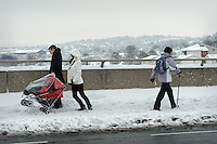 A young couple with a pushchair walk over the bridge after an  early winter snow fall.