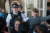 Police officers watch as Blue 9 private security guards prevent protesters from entering Hendon Town Hall through a window.  Tenants, evicted tenants and housing campaigners in Barnet, north London, protest over the sale of West Hendon estate and the demolition of Sweets Way estate.