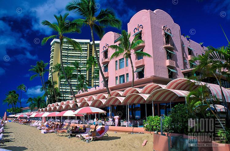 "The pink and white signature umbrellas line the beach at the fabulous Royal Hawaiian Hotel, or """"pink palace"""", a Waikiki historic landmark."