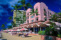 "The pink and white signature umbrellas line the beach at the fabulous Royal Hawaiian Hotel, or """"pink palace"""", a Waikiki historic landmark."