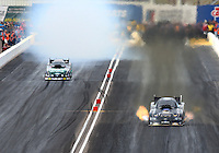 Feb 23, 2014; Chandler, AZ, USA; NHRA funny car driver Alexis DeJoria (right) takes the win over a tire smoking John Force during the Carquest Auto Parts Nationals at Wild Horse Motorsports Park. Mandatory Credit: Mark J. Rebilas-USA TODAY Sports